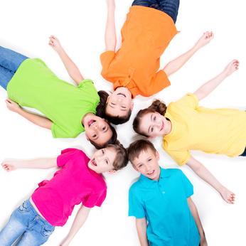 Five smiling children lying on the floor.